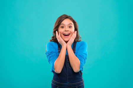 Sincere excitement. Kid girl long healthy shiny hair wear casual clothes. Little girl excited happy face. Kid happy cute face feels excited blue background. Exciting moments. Excitement emotion.