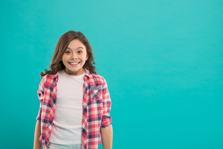 Sincere excitement. Kid girl long healthy shiny hair wear casual clothes. Exciting moments. Little girl excited happy face. Kid happy cute face feels excited blue background. Excitement emotion.