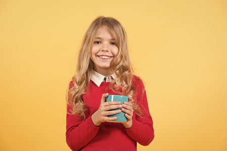 Thirst, dehydration concept. Health and healthy drink. Tea or coffee break. Girl with long blond hair in red sweater hold mug. Child smile with blue cup on orange background.