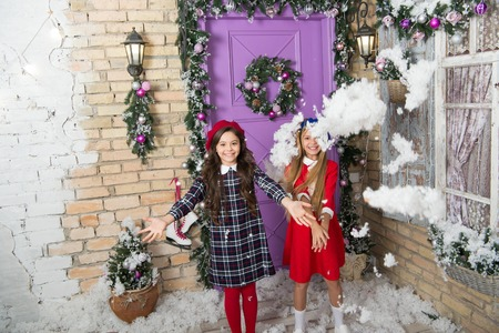 Photo for December fun. Childhood games on winter holidays. Small girls with Christmas decoration. Happy children celebrate Christmas and new year. Small children throw artificial snow. Winter fun. - Royalty Free Image