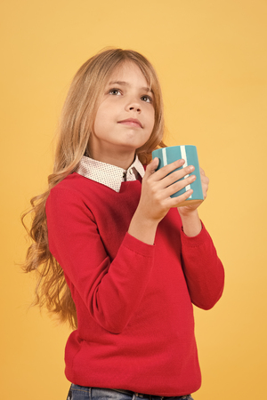 Health and healthy drink. Girl with long blond hair in red sweater with mug. Child with serious face hold blue cup on orange background. Tea or coffee break. Thirst, dehydration concept.