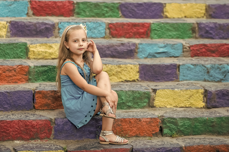 Photo pour small baby girl or cute child with adorable face and bow in blonde hair in blue dress outdoor sitting on colorful stony stairs background, copy space - image libre de droit