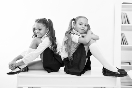 Photo for School break concept. Schoolgirls cute pony tails hairstyle sit on desk. Best friends free relaxing after classes. Perfect schoolgirls with tidy fancy hair relaxing or having rest after lessons. - Royalty Free Image