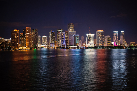 Photo pour Miami city skyline panorama at night, usa. Skyscrapers illumination reflect on sea water in dusk. Architecture, structure, design. Building, construction, development. Wanderlust travel discovery - image libre de droit