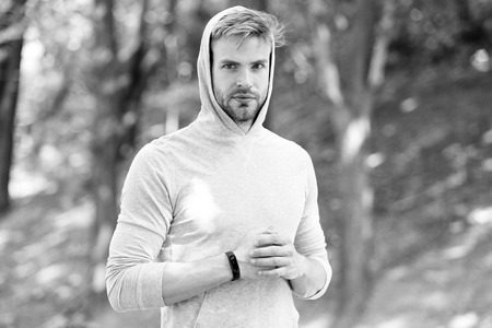 Photo pour Jogging his way to good health. Sportsman training with pedometer gadget. Athlete with fitness tracker or pedometer ready for workout. Man athlete strict face with sport equipment nature background. - image libre de droit