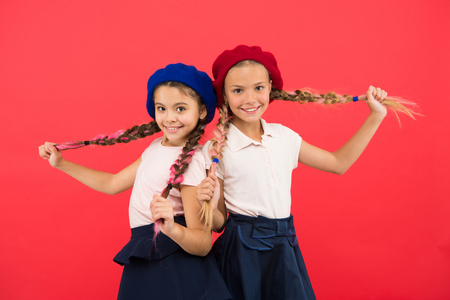 Photo pour Loving their new style. Small children with long hair plaits. French style girls. Cute girls having the same hairstyle. Fashion girls with tied hair into braids. Little kids wearing french berets. - image libre de droit