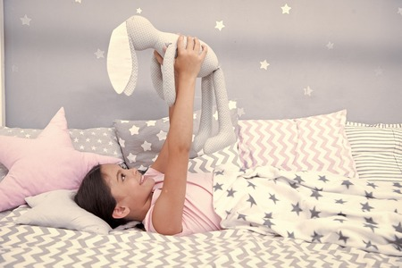 Photo pour Best friends. Girl child lay on bed with grey bunny toy in her bedroom. Kid prepare to go to bed. Wish sweet dreams to favorite toy. Girl kid relax and play bunny toy before fall asleep. - image libre de droit