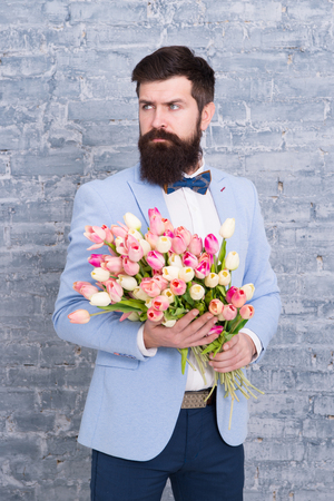 Foto de We take flowers personally. Spring gift. Bearded man hipster with flowers. Love. international holiday. Womens day. March 8. Bearded man with tulip spring bouquet. Spring time. enjoying spring. - Imagen libre de derechos