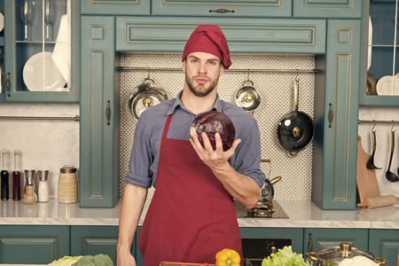 Photo pour Confident at kitchen. Take old favorites and make healthful substitutions. Take favorite recipes and lighten them up. Man handsome chef holds violet cabbage thinking what healthy dish to cook. - image libre de droit
