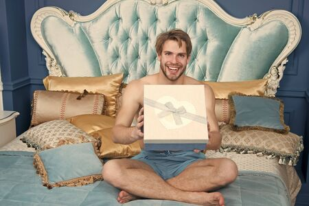Already found his birthday gift in bed. Happy man holding present wrapped in box. Sexy man smiling with birthday gift. Handsome guy with box on birthday morning. Happy birthday to you.