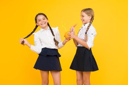 Photo for Say yes to health. Small schoolchildren drinking juice from orange fruits for their health on yellow background. Nutrition for kids health. Drinking juice can boost your health - Royalty Free Image