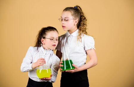 Photo pour little smart girls with testing flask. back to school. knowledge and education. children study at biology lesson. science research in lab. chemistry flask with liquid. testing flask in hands of kids - image libre de droit