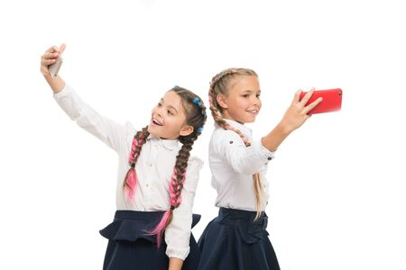 Photo pour True selfie stars. Happy small schoolgirls taking selfie with smartphones isolated on white. Little children smiling to selfie cameras in mobile phones. Enjoying selfie session on september 1 - image libre de droit