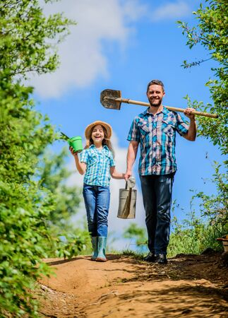 Photo pour Father and daughter with shovel and watering can. Spring gardening checklist. It is time to plant prepare beds and care for lawn. Pick out flats favorite plants. Gardening pro tips. Spring gardening - image libre de droit