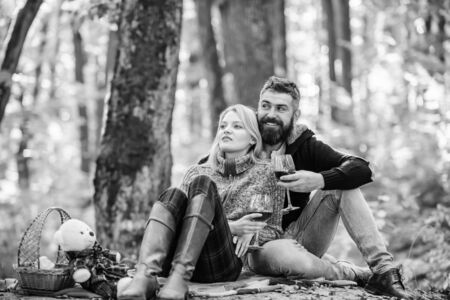 Photo pour Couple in love celebrate anniversary picnic date. Couple cuddling drinking wine. Enjoying their perfect date. Happy loving couple relaxing in park together. Romantic picnic with wine in forest - image libre de droit