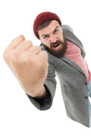 Casual and informal. Bearded man in casual style shaking his fist with anger. Fashion male model wearing casual jacket with red hat. Angry hipster with beard and moustache looking casual