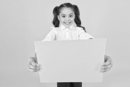 Photo pour Being given a home work. Little child holding empty sheet for examination work on yellow background. Small girl with blank green paper for project work or research. Paper work, copy space - image libre de droit