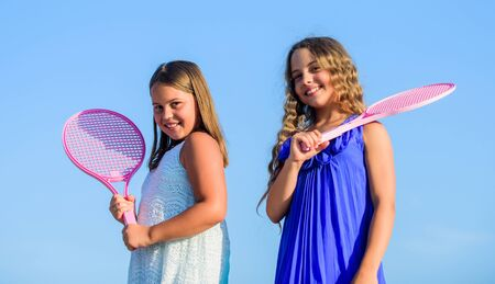 Sport is our life. small girls with tennis racquet. summer sport activity. energetic children. happy and cheerful. sporty game playing. summer games. play tennis. childhood happiness and sisterhood