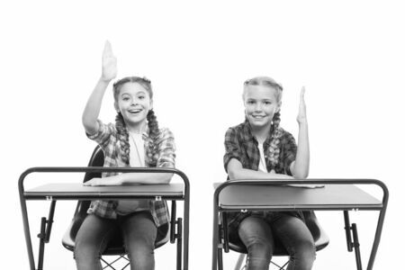 Photo for Free or private schooling. Little children enjoy home schooling. Small schoolgirls having compulsory schooling. Adorable kids with raised hands sitting at desks isolated on white. Schooling years - Royalty Free Image