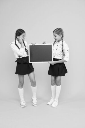 Photo for A reusable writing surface. Little children preparing blackboard for lesson. Small pupils with school blackboard. Cute girls holding blackboard on yellow background. Blank blackboard, copy space - Royalty Free Image