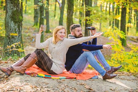 Look there. Relaxing in park together. Happy loving couple relaxing in park together. Couple in love tourists relaxing picnic blanket. Man with binoculars and woman with metal mug enjoy nature park