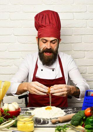 Photo pour Man with beard breaks egg into flour on white background - image libre de droit