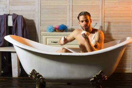 Photo pour Macho playing with foam in bathtub. Guy in bathroom - image libre de droit