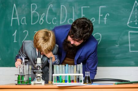 We have appreciation for innovation. son and father at school. Wisdom. Back to school. Chemistry and physics biology. Flask in scientist hand with Test tubes. small boy with teacher man.