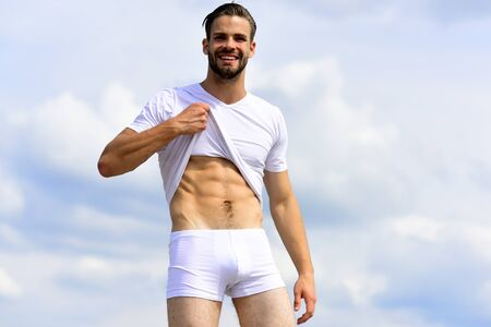 Photo pour Man with unshaved and happy face demonstrates naked abs - image libre de droit