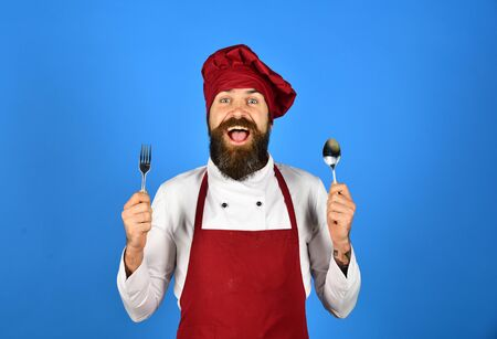 Photo pour Chef with mustache and smile holds metal spoon and fork. - image libre de droit