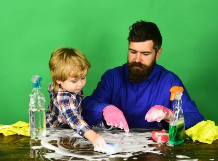 Man with beard and child in checkered shirt cleaning together