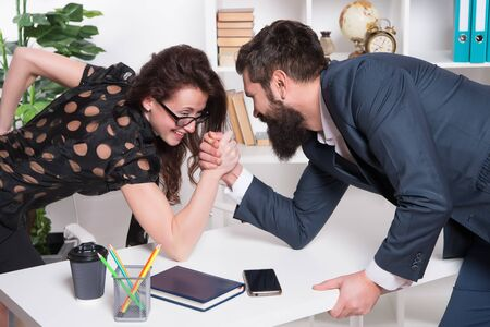 Foto de Whos stronger. Bearded man and sexy woman arm wrestle in office. Workplace relationship. Competitive relationship. Relationship between business partners. Professional couple. Relationship or rivalry - Imagen libre de derechos