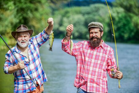 Photo pour Reunited and it feel so good. father and son fishing. summer weekend. mature men fisher. hobby and sport activity. Trout bait. two happy fisherman with fishing rods. male friendship. family bonding - image libre de droit