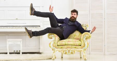 Photo for Macho attractive and elegant on cheerful face and happy expression. Playful mood concept. Man with beard and mustache wearing fashionable classic suit, sits, jumps on old fashioned armchair - Royalty Free Image