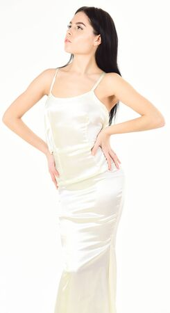Foto de Lady on calm face wears expensive fashionable evening dress. Slim and fit concept. Fashion model with slim figure as result of dieting and fitness. Woman in elegant white dress, white background. - Imagen libre de derechos
