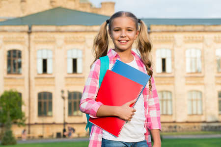 Photo pour little smart student. happy preschool girl with folder in school yard. back to school. hardworking child with book. concept of education. time to work hard. cute girl study outdoor. Care About Kids. - image libre de droit