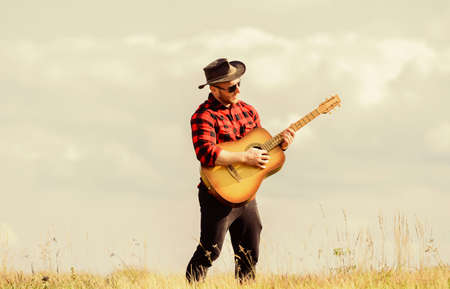 Photo for Play beautiful melody. Country music concept. Guitarist country singer stand in field sky background. Inspired country musician. Hiking song. Handsome man with guitar. Country style. Summer vacation - Royalty Free Image