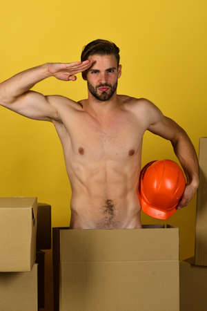 Foto per Guy with sexy torso and orange hardhat saluting with hand - Immagine Royalty Free