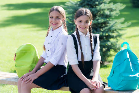 Exams. happy childrens day. childhood hapiness. two sisters in school uniform outdoor. ready for holidays. happy teen kids carry backpack. back to school. small school girls walking in spring