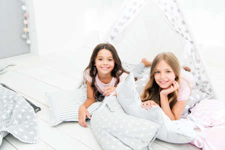 Photo pour Pajamas party for kids. Siblings best friends. Sisters or best friends spend time together in bedroom. Girls having fun together. Girlish leisure. Sisters friends share gossips having fun at home - image libre de droit