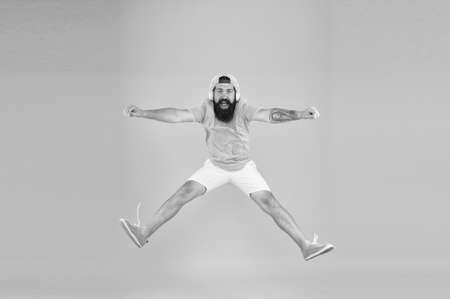 Photo pour bearded man listen music. happy guy wear headphones. summer vacation party. brutal hipster jump high. his favorite song. mature dj full of energy. feel freedom. celebrating success - image libre de droit