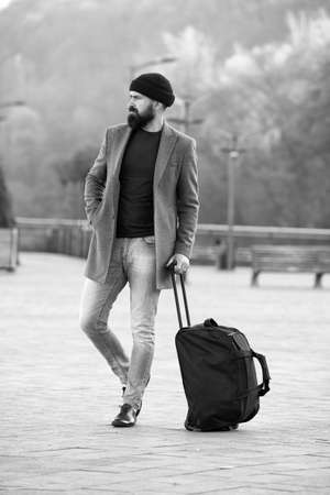 Photo for Ready to travel. Carry travel bag. Business trip. Man bearded hipster travel with big luggage bag on wheels. Let travel begin. Traveler with suitcase waiting transportation to airport railway station - Royalty Free Image