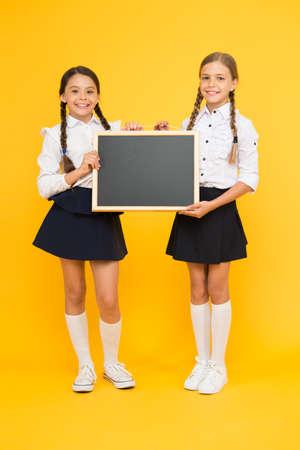 Photo for Little but smart. Little schoolchildren holding blackboard on yellow background. Little children with black-board for education. Little girls with school chalkboard, copy space - Royalty Free Image