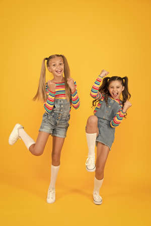 Photo pour free and energetic beauty. happy childhood. real friendship. best friends forever. small sisters have fun. little girls jump yellow background. sense of freedom. finally summer vacation - image libre de droit