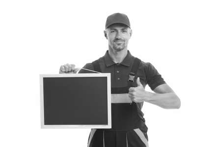 He loves his job. male worker in cap hold blackboard. board for copy space. builder service advertisement. best offer ever. move out or relocation loader. qualified repairman offers his services