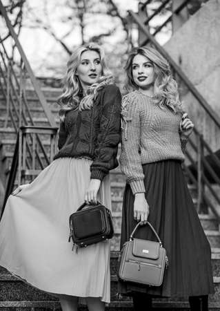 Photo pour Girls blonde wear matching clothes. Matching outfits. Women sisters outdoors stairs background. Matching colors. Personal stylist service. Sweater skirt trend. Completing each other - image libre de droit