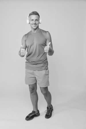 Enjoy workout routine. Sportsman give thumbs ups listening to music. Using motivation to enjoy exercising. Sport and fitness. Enjoy active lifestyle. Enjoy life after training