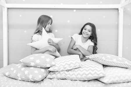 Photo pour Happy childhood. Happy children have fun in bed. Little girls play with cushions. Enjoying childhood years. Childhood protection. Childcare center. Childrens day. Childhood only happens once - image libre de droit