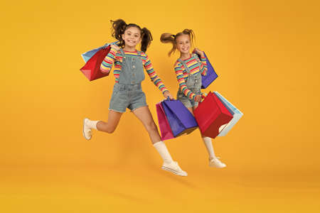 Photo pour Towards purchase. Modern fashion. Kids fashion. Cute children hurry up for sale season. Discount and sale. Little girls carry shopping bags. Matching outfits. Trendy and fancy. Fashion shop - image libre de droit