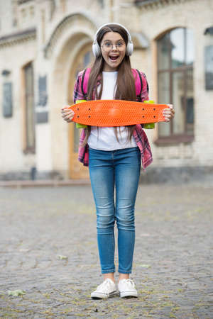 Perfect travel skateboard. Happy girl hold penny board urban outdoors. Summer travel. Transportation. Sport and recreation. Recreational activity. Healthy lifestyle. Street culture. Music